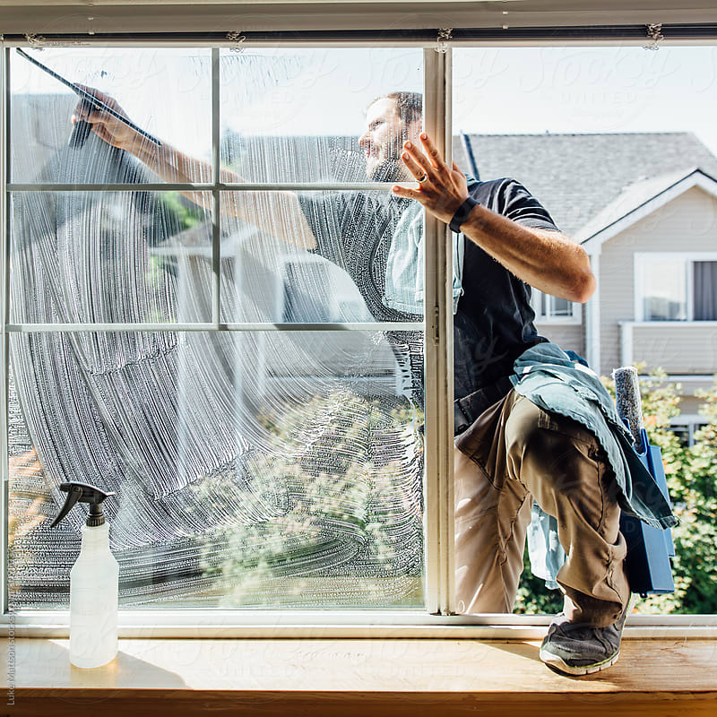 Window Washer Cleaning Outside Of Bedroom Window At Condo by Luke Mattson for Stocksy United