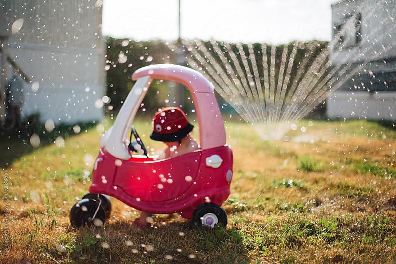 Child sitting in car in sprinkler by Jessica Byrum for Stocksy United