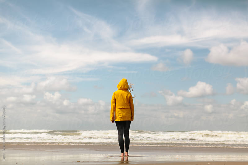 Person looks over the ocean on a windy beach wearing a yellow raincoat by Denni Van Huis for Stocksy United