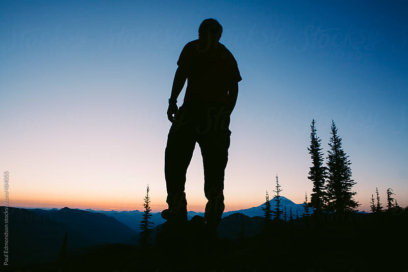 Silhouette of man standing on mountain summit at dusk, Mt. Rainier in distance by Paul Edmondson for Stocksy United