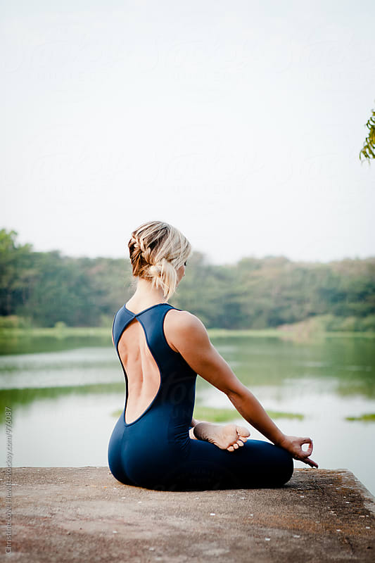 Woman doing yoga at a lake by Christine Hewitt for Stocksy United
