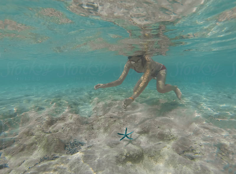 Girl leaving a sea star in the ocean by Beatrix Boros for Stocksy United