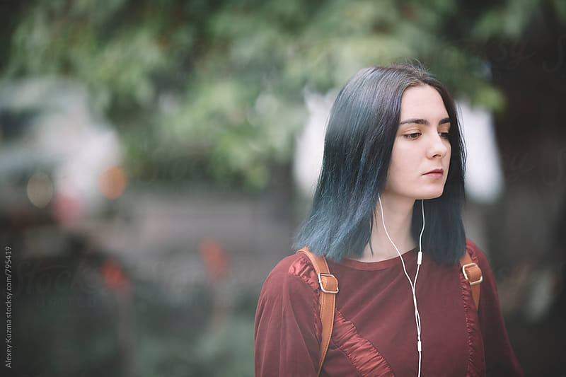 young woman with blue hair walking on the street by Alexey Kuzma for Stocksy United