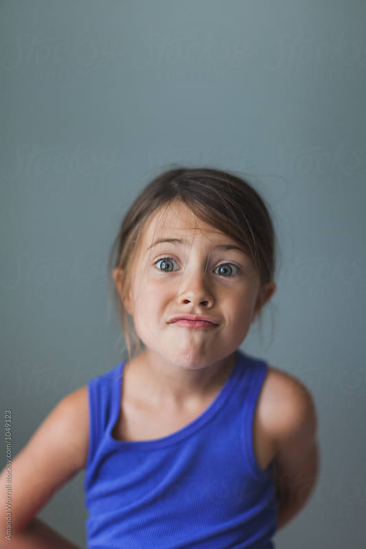 Silly kindergarten girl making a goofy expression by Amanda Worrall for Stocksy United