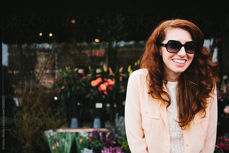 Beautiful woman with red hair smiling outside a flower shop by We Are SISU for Stocksy United