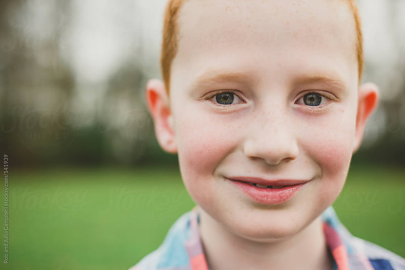 Portrait of a cute young boy smiling in a field by Rob and Julia Campbell for Stocksy United