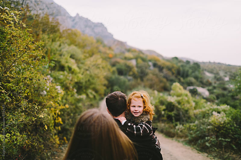 Father carrying his daughter peering over his shoulder by Evgenij Yulkin for Stocksy United