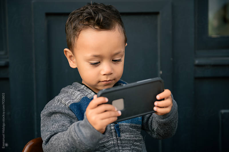 Toddler boy holding a smart phone and watching by Emmanuel Hidalgo for Stocksy United