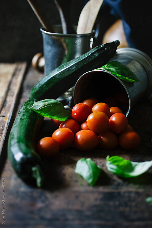 Tomato,courgette and basil ingredients on a table. by Darren Muir for Stocksy United