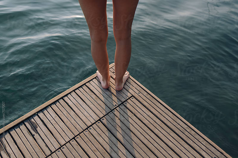 Detail of the legs of a woman standing at the edge of the pier by michela ravasio for Stocksy United