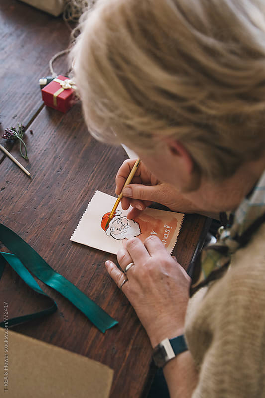 Woman painting Christmas card by Danil Nevsky for Stocksy United