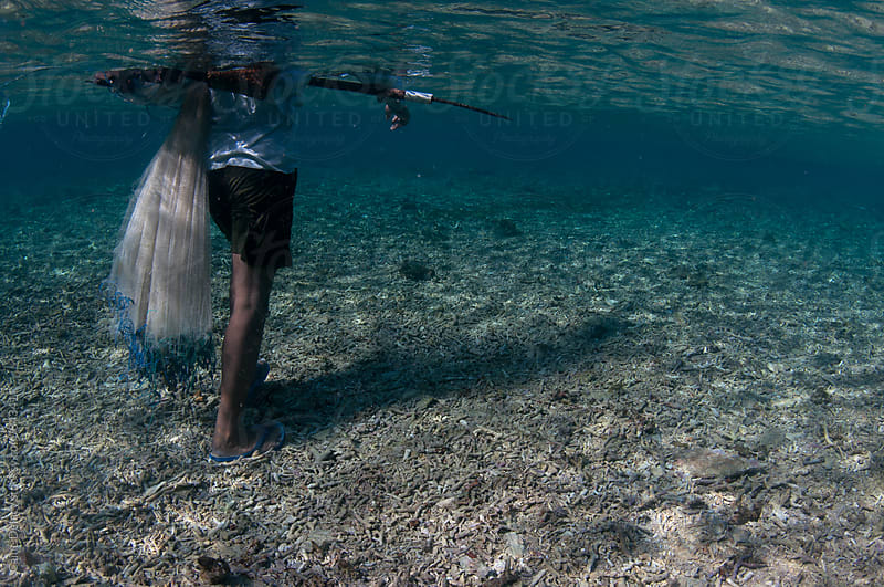 Traditional fisherman walks over broken and damaged coral reef by Caine Delacy for Stocksy United