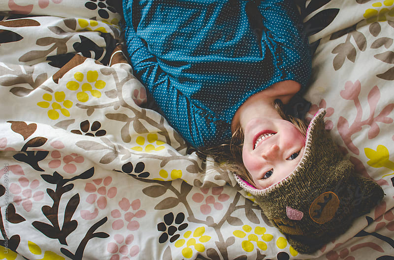 Cute little girl in owl hat lying on bed and smiling by Lindsay Crandall for Stocksy United