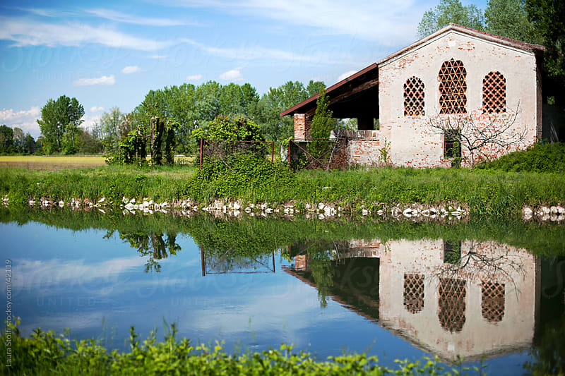 Abandoned ancient italian farm on river shore and its reflection by Laura Stolfi for Stocksy United