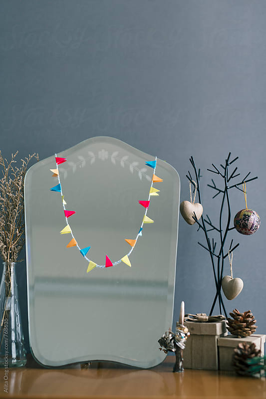 Colourful bunting on mirror by Alita Ong for Stocksy United