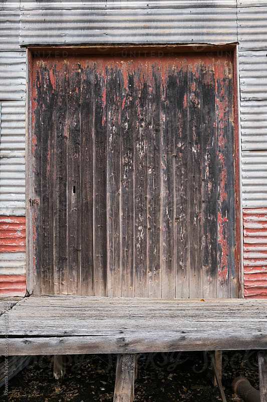Rustic timber door to old warehouse by Rowena Naylor for Stocksy United