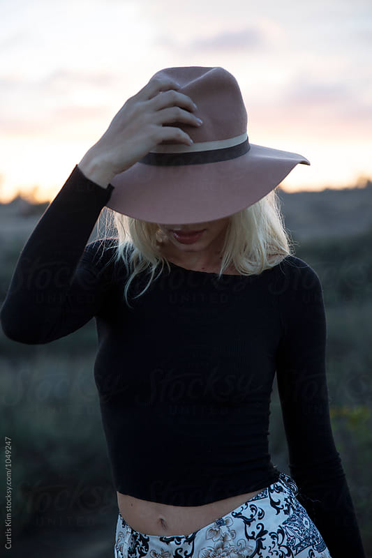 Woman holding her hat during sunset by Curtis Kim for Stocksy United