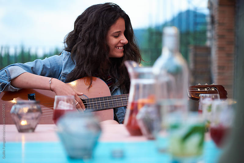 smiling brunette playing guitar at outdoor party by Guille Faingold for Stocksy United