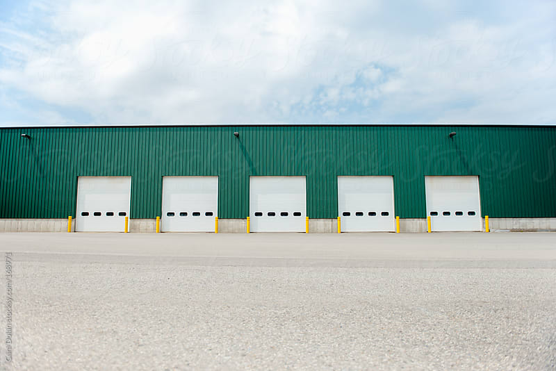 Large industrial warehouse with 5 garage doors by Cara Dolan for Stocksy United