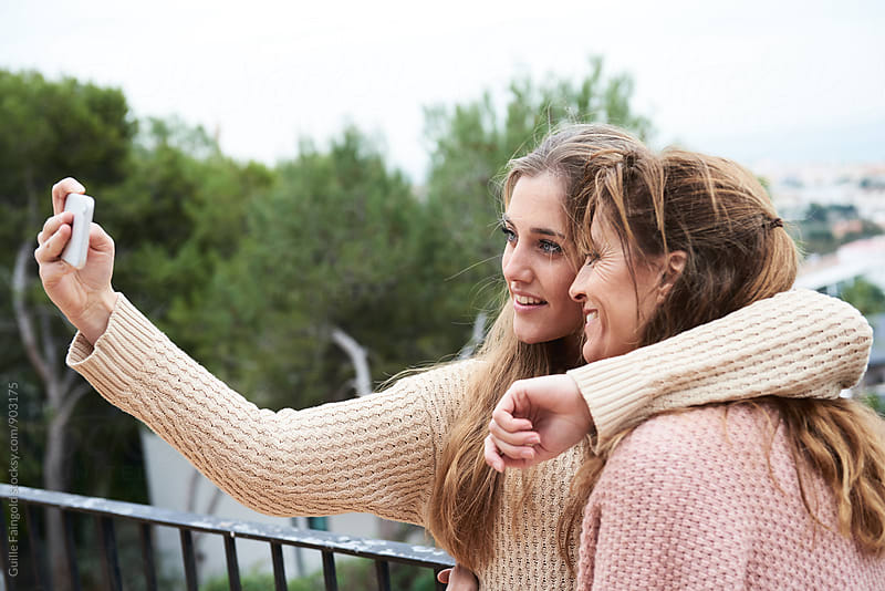 Woman hugging her mother while making selfie by Guille Faingold for Stocksy United
