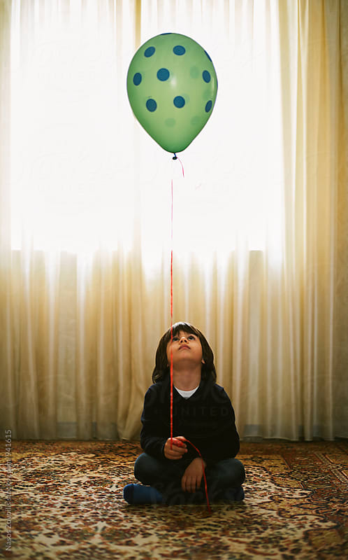 5 years old boy holding a balloon indoor by Nasos Zovoilis for Stocksy United