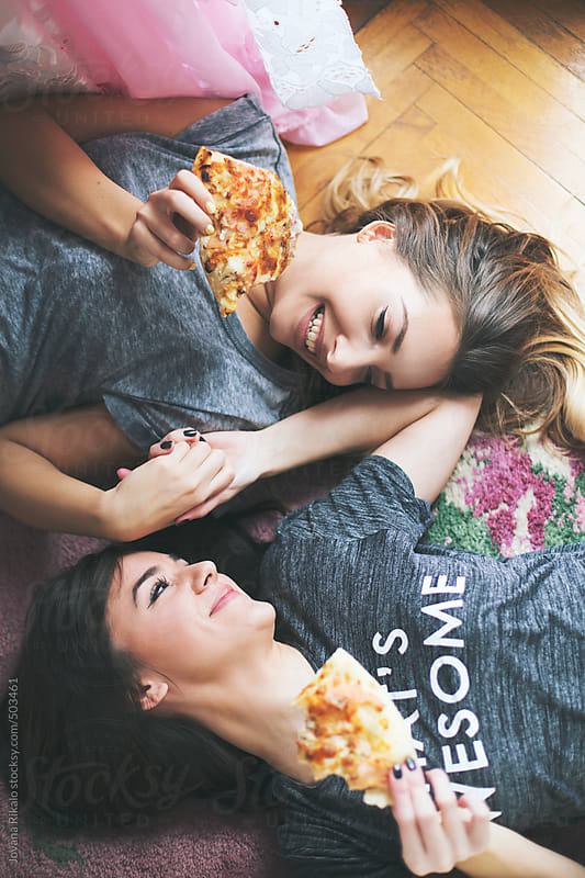 Two young female friends eating pizza by Jovana Rikalo for Stocksy United