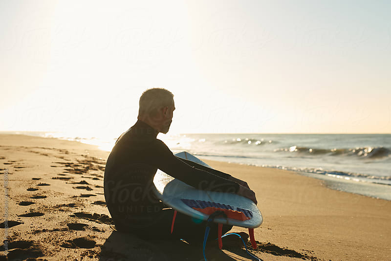 Side view of surfer with board on beach by Guille Faingold for Stocksy United