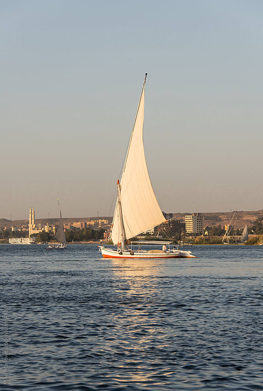 A boat sailing on the Nile at sunset. by Mike Marlowe for Stocksy United