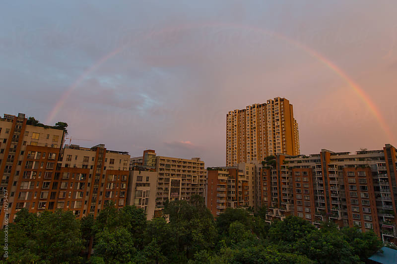 rainbow in the city sky by Bo Bo for Stocksy United