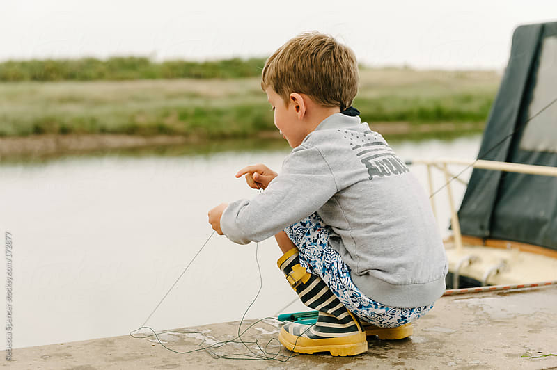 Young boy with fishing line dipping for crabs by Rebecca Spencer for Stocksy United