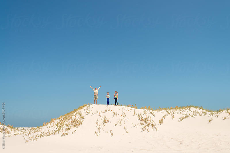 jumping the sand dunes, a father with his 2 daughters by Gillian Vann for Stocksy United