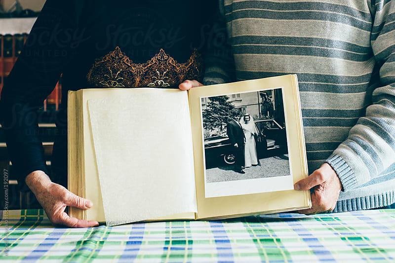 Elderly couple holding their wedding album by michela ravasio for Stocksy United