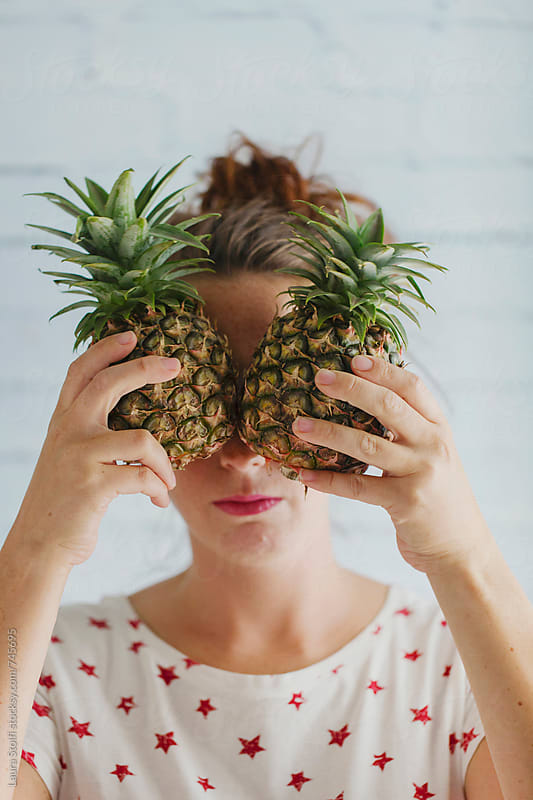 Pineapple face: beautiful young woman hides her eyes behind mini pineapples by Laura Stolfi for Stocksy United