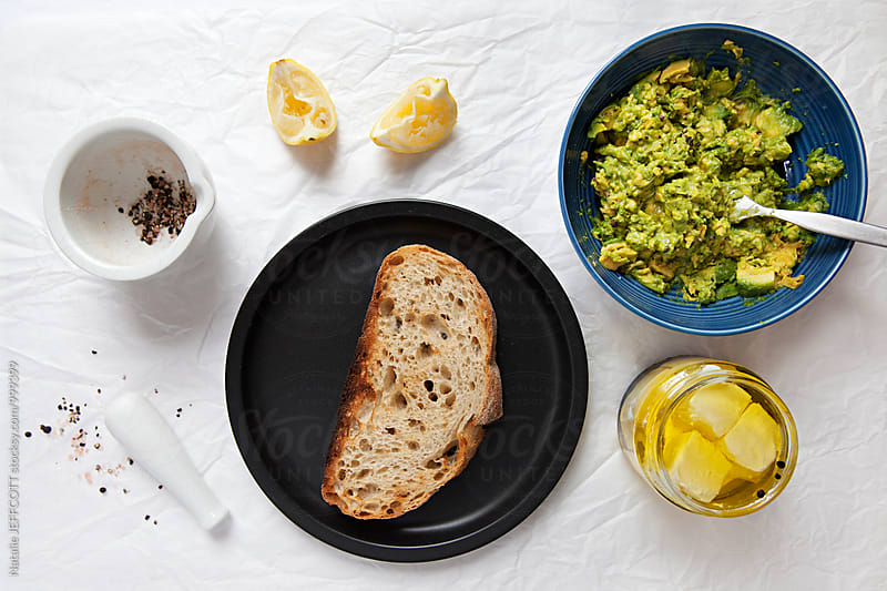 Making smashed avocado on toast with feta for breakfast by Natalie JEFFCOTT for Stocksy United