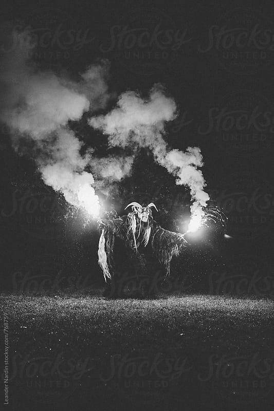 krampus with burning bengal light on a meadow by Leander Nardin for Stocksy United