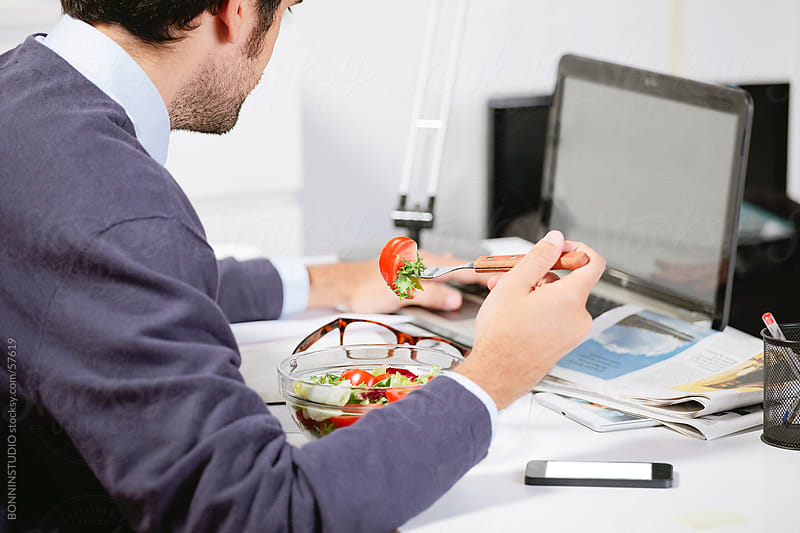 Young creative designer working and eating salad by BONNINSTUDIO for Stocksy United