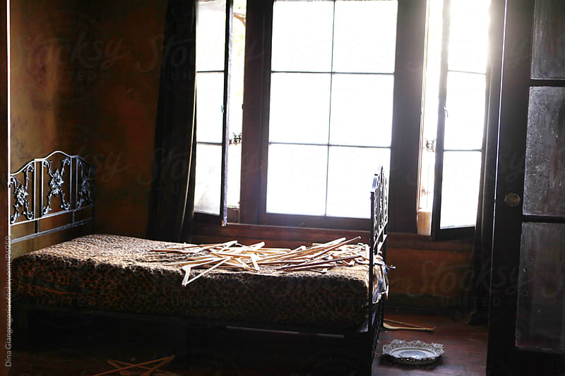 Empty bed near window with a pile of wooden hangers by Dina Giangregorio for Stocksy United