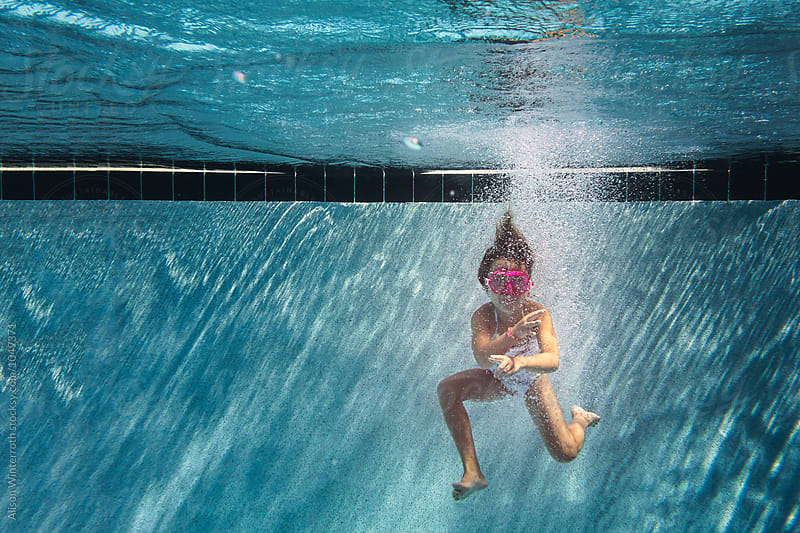 A Young Girl Jumps Into The Water In A Blue Pool by Alison Winterroth for Stocksy United