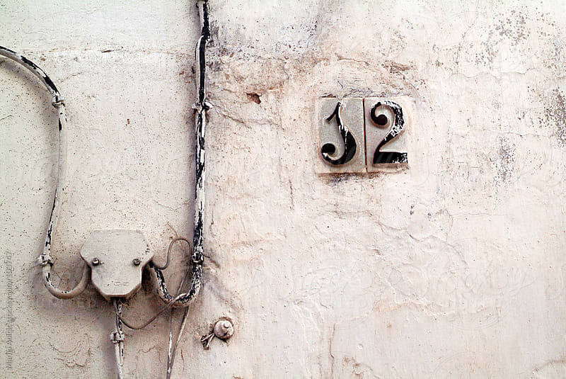 streets numbers on old grungy facades   by Marija Anicic for Stocksy United