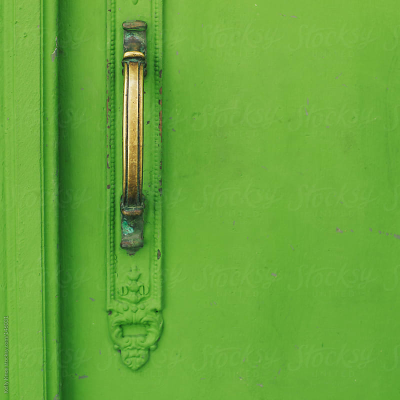 detail of an old door painted green by Kelly Knox for Stocksy United