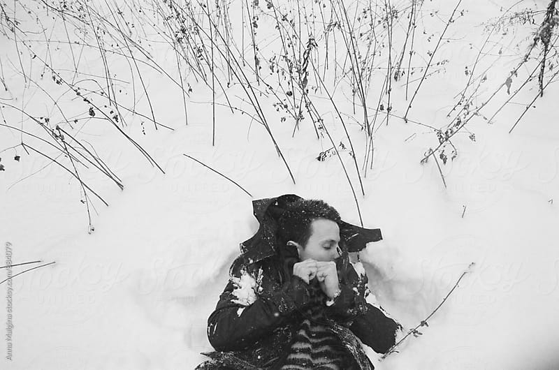 A black and white film portrait of young man lying on the snow by Anna Malgina for Stocksy United