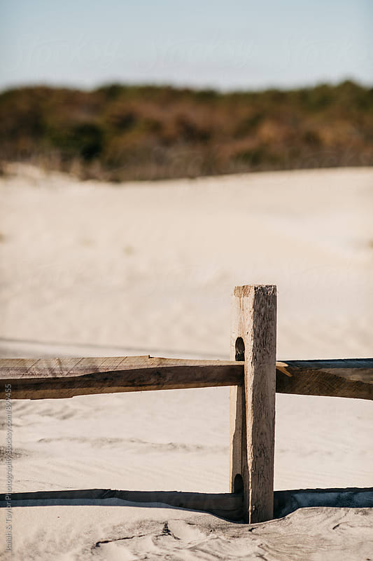 Fence in sand by Isaiah & Taylor Photography for Stocksy United