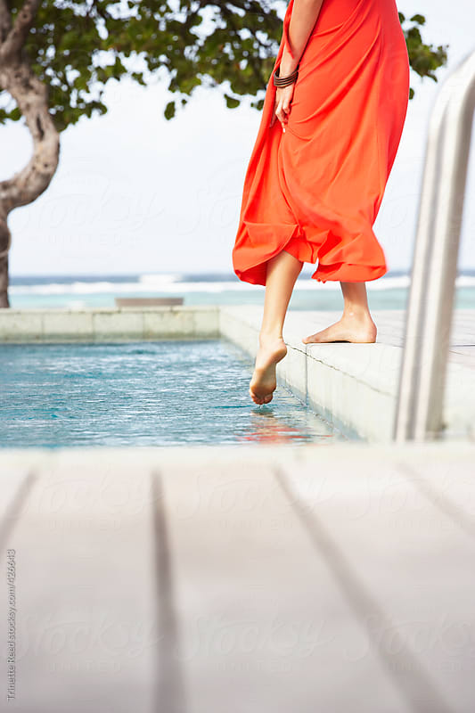 Woman dipping her foot in pool at luxury resort by Trinette Reed for Stocksy United