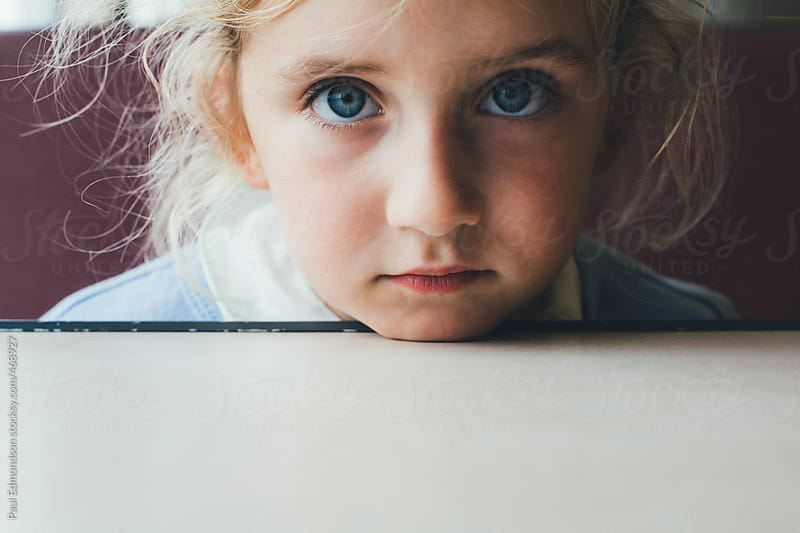 Portrait of cute four year old girl, leaning chin on table by Paul Edmondson for Stocksy United