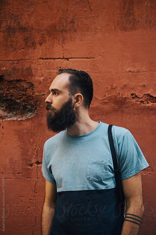 Portrait of a Handsome Bearded Man in Front of the Red Wall by Katarina Radovic for Stocksy United