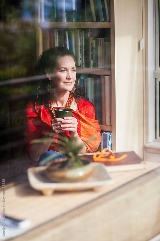 Middle age woman holding a mug looking out of the window by Suprijono Suharjoto for Stocksy United