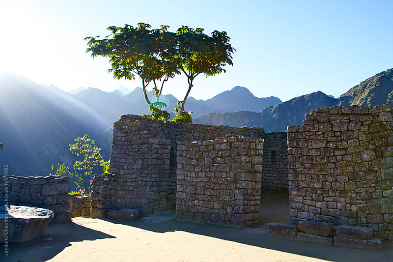 Sun shinning down on inca stone house ruins, with mountains in the background, Machu Picchu, Peru by Jaydene Chapman for Stocksy United