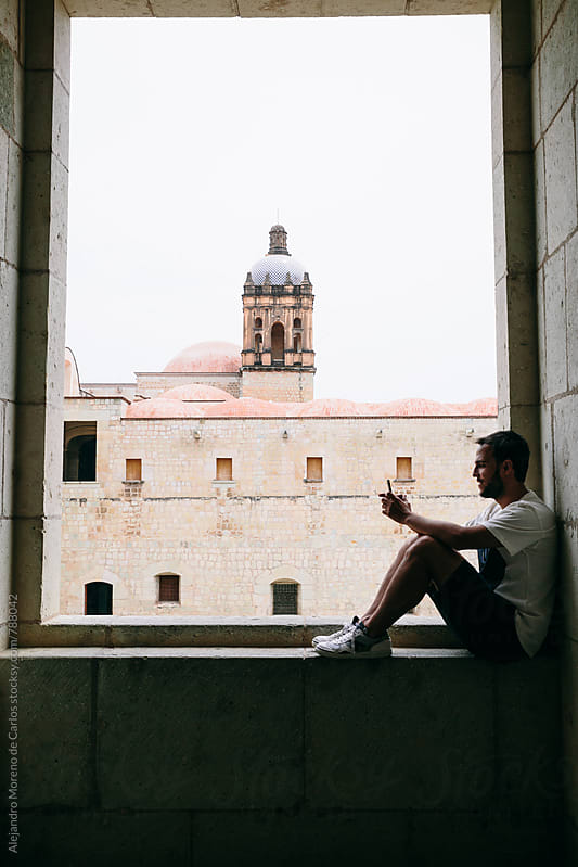 Young man sitting on a stone wall inside a lookout window with views by Alejandro Moreno de Carlos for Stocksy United