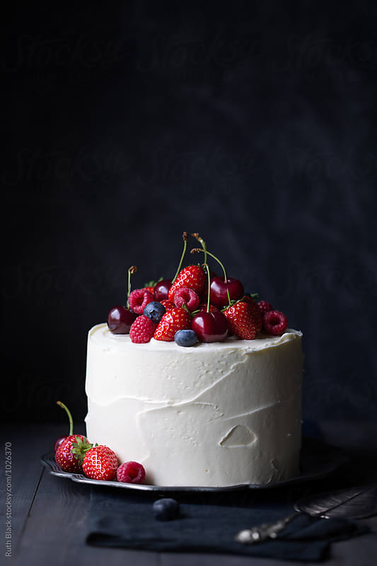 Cake decorated with fresh berries by Ruth Black for Stocksy United