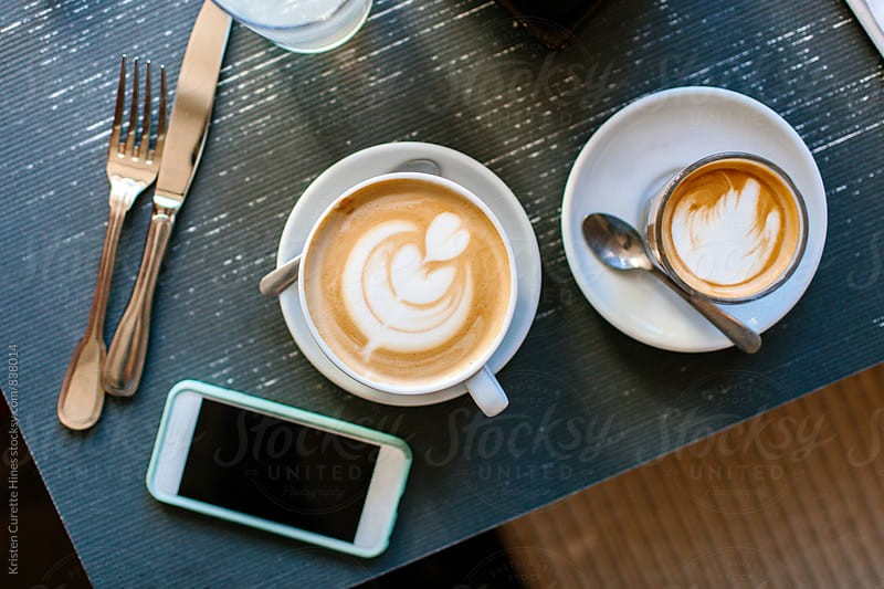 A cell phone laying on a breakfast table by a latte and espresso  by Kristen Curette Hines for Stocksy United